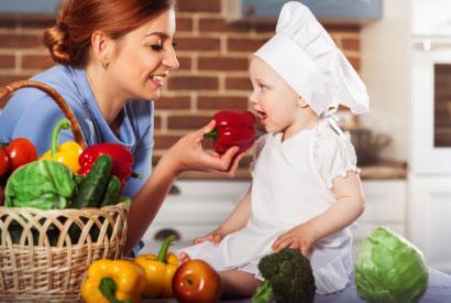 Femme faisant semblant de donner à manger un poivron à un bébé